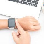 woman touching smart watch hand on work desk