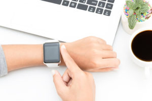 woman touching smart watch hand on work desk